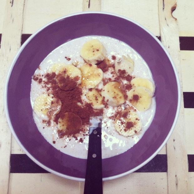 Yummy summer oat bowl with almonds, maple syrup, banana and raw cacao